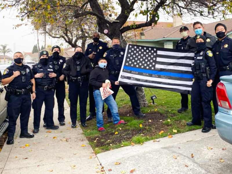 "Members of the Vallejo Police Department, including Chief Shawny Williams, Deputy Chief Michael Kihmm, and Captain Jason Potts pose for a photograph with the controversial ""Blue Lives Matter"" flag, which has been criticized for its associations with the white supremacist movement. The Vallejo Police Department posted the image to its official social media accounts on Dec. 25, 2020, but deleted it from Twitter following criticism. The photograph remains on the department's official Facebook and Instagram pages."