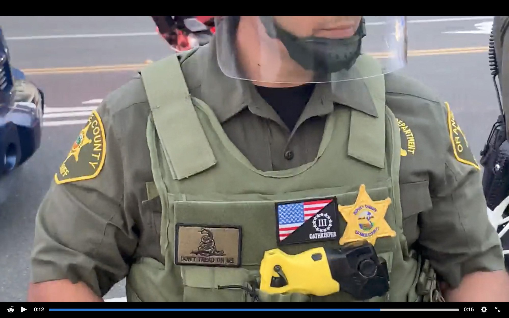 A closeup image of a male Orange County sheriff's deputy in uniform, to which he has affixed two unauthorized far-right patches.