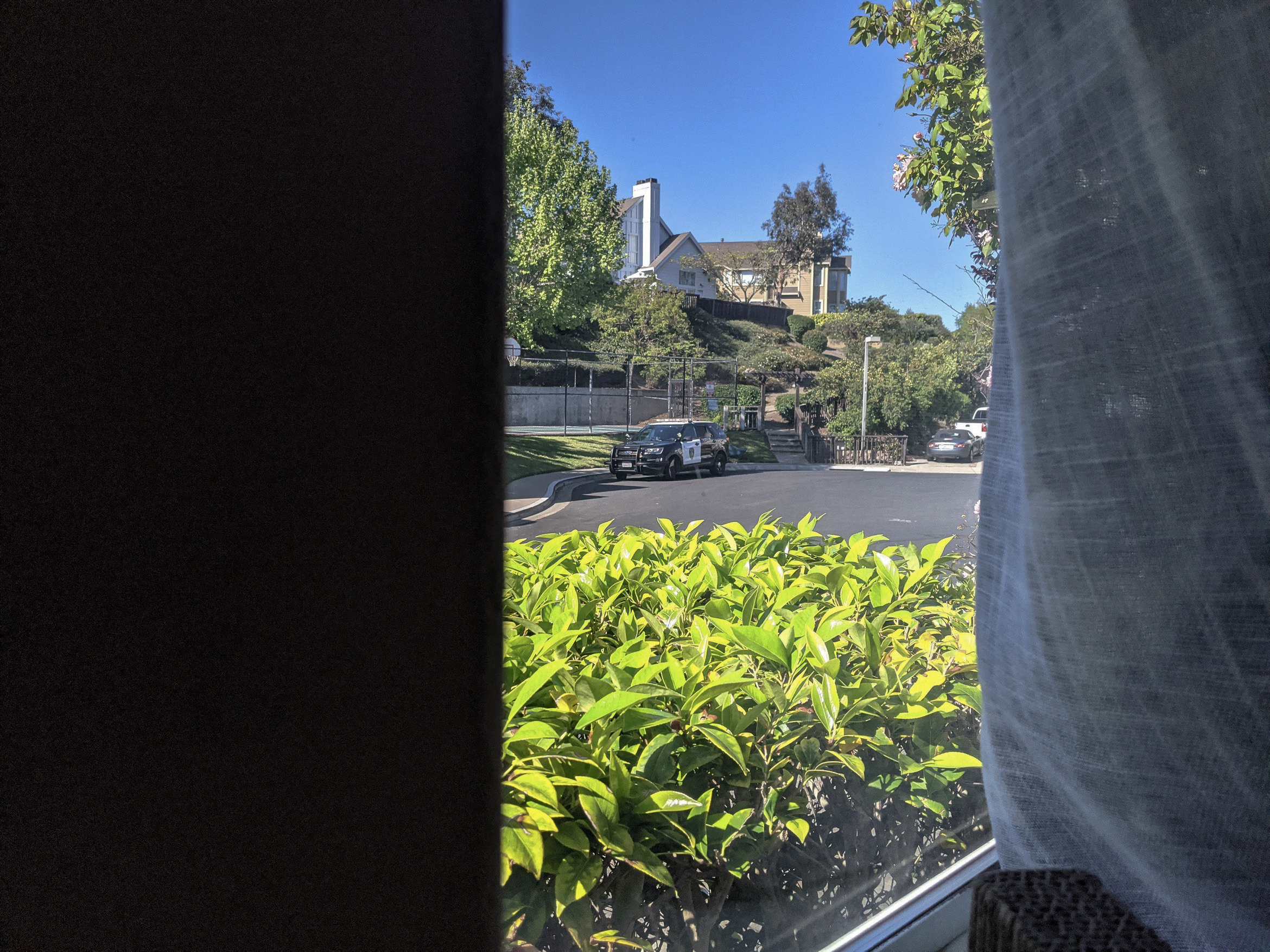 A Vallejo Police Department SUV is seen parked outside fired City Hall employee Slater Matzke's home. The photograph was taken through a window from inside the home.