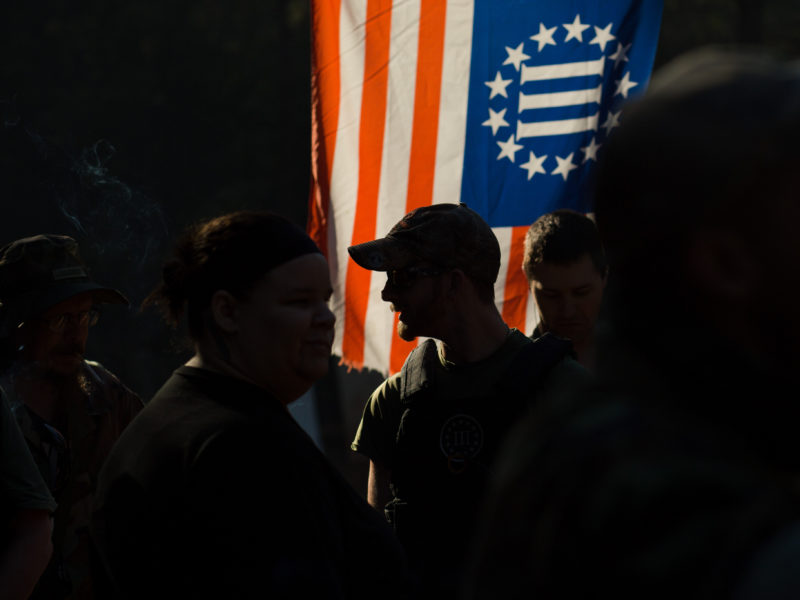 """A man stands among a crowd of people in silhouette against a backlit flag of the """"Three Percenter"""" militia."""