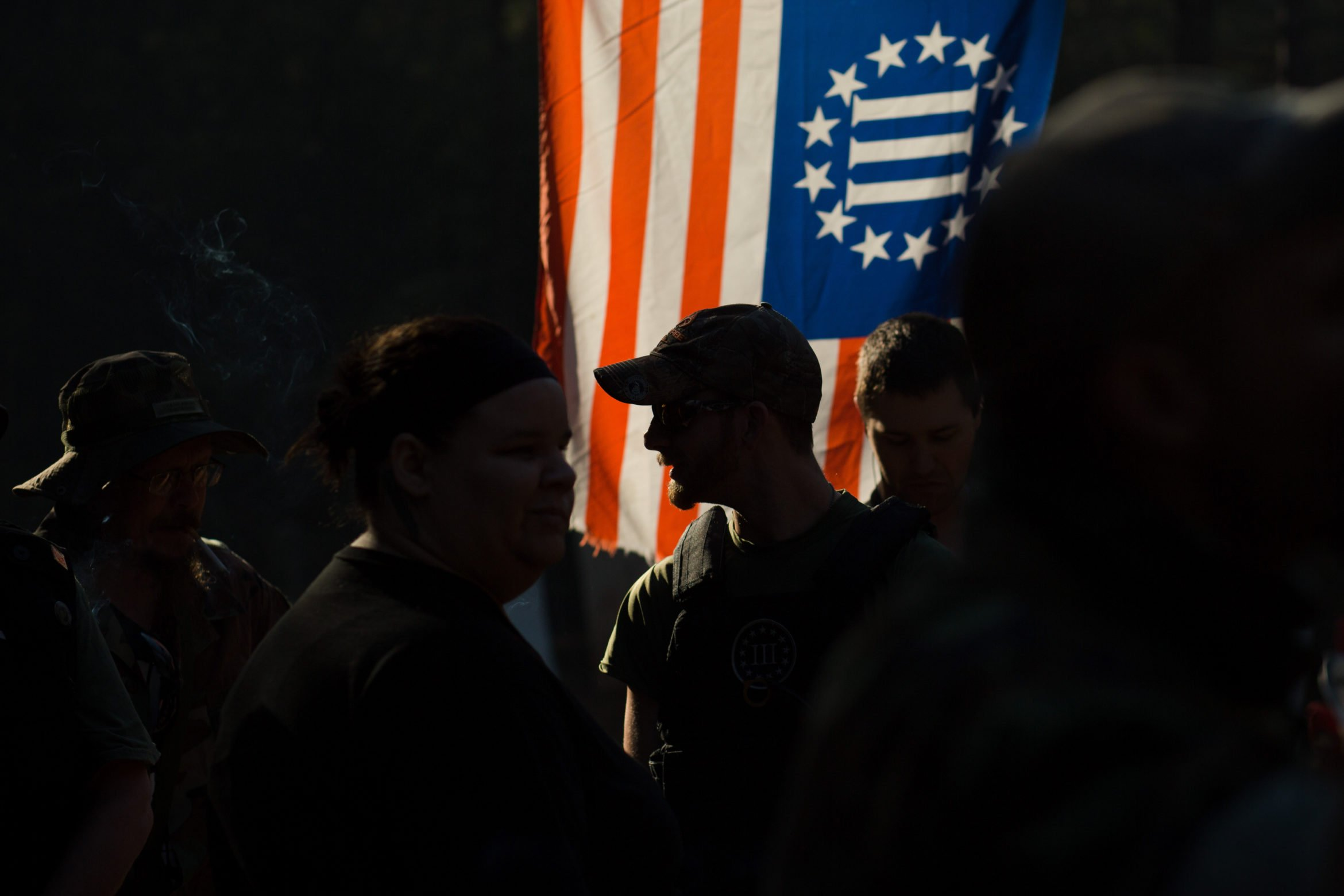 "A man stands among a crowd of people in silhouette against a backlit flag of the ""Three Percenter"" militia."
