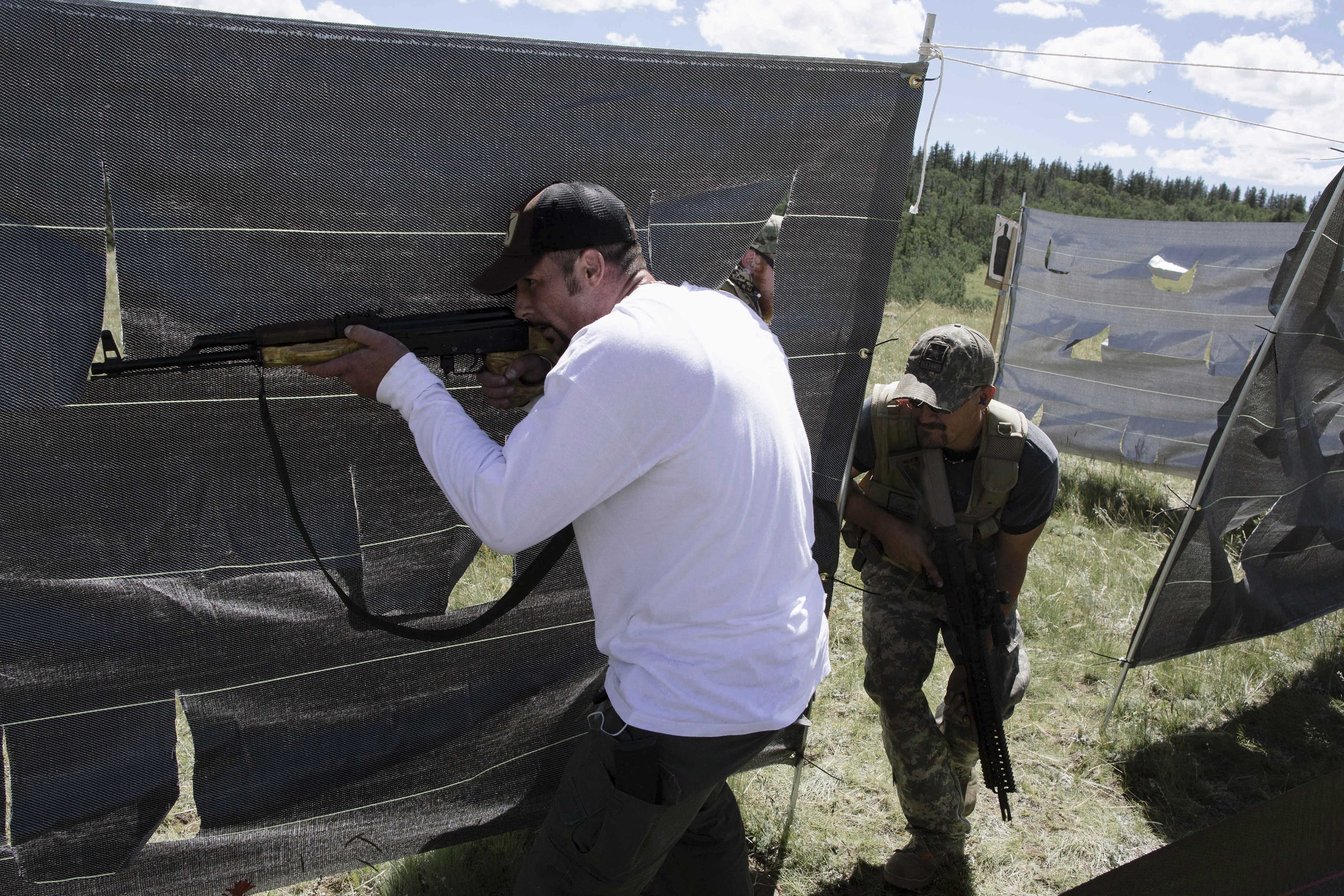Two men holding semiautomatic rifles move through an outdoor close quarters battle (CQB) course during a militia drill outside Denver, Colorado in 2015.