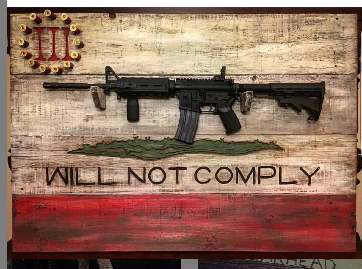 """An AR-15 rifle on a display rack bearing the words, """"WILL NOT COMPLY"""" and the logo of the Three Percenters, a far-right militia linked to violence across the country."""