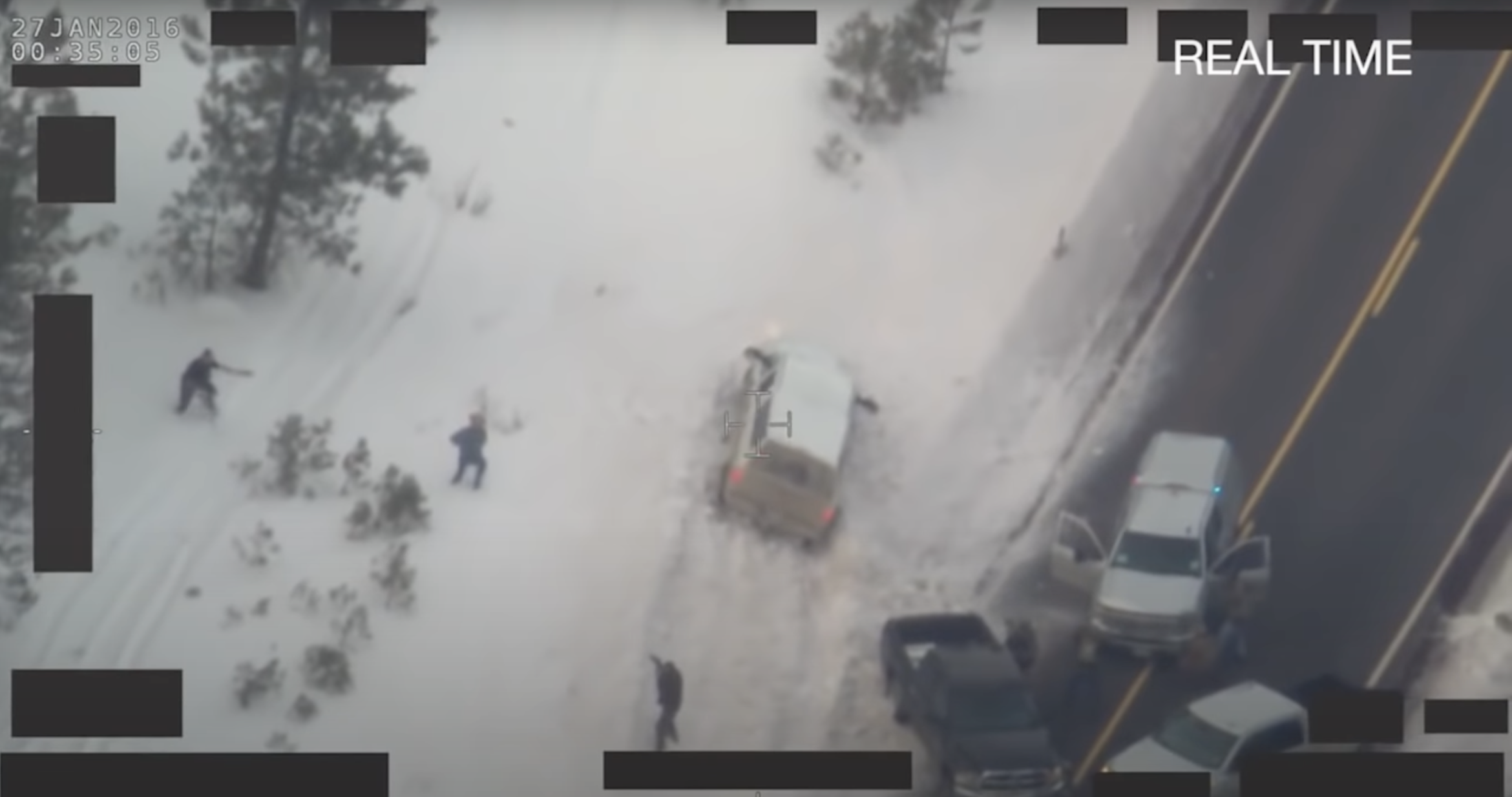 Overhead view from an FBI surveillance helicopter of several figures standing in the snow. One man is flanked by two law enforcement officers who are pointing weapons at him.